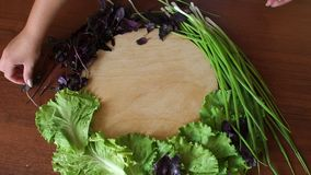 Cutting board with a spread out around vegetables, girl puts onions and lettuce. Fresh vegetables and herbs on wooden table and empty cutting board, women puts stock video