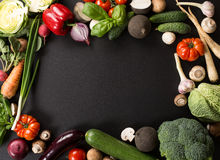 Fresh vegetables. And ingredients for cooking around vintage cutting board on black background stock photography