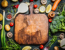 Fresh vegetables and ingredients for cooking around vintage cutting board on rustic background, top view, place for text. royalty free stock photography