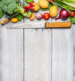 Fresh vegetables ingredients for cooking with used kitchen knife on white wooden background, top view, place for text. Stock Image