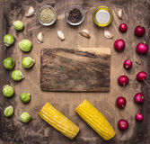 Fresh vegetables ingredients radishes, brussels sprouts, corn, seasoning lined around the cutting board  wooden rustic backgroun. Fresh vegetables ingredients Royalty Free Stock Photography