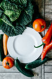 Fresh vegetables: kale, Carrot, pepper, tomato, cucumber around. Empty plate on a wooden background. Healthy, vegetarian, organic food Stock Photos