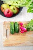 Fresh vegetables in the kitchen. With a high angle view of a bowl containing fresh apples and celery alongside a chopping board with radish and cucumber for Royalty Free Stock Photos