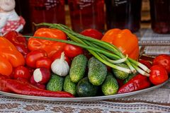 Fresh vegetables on a large plate stand on a table covered with a tablecloth Stock Photo