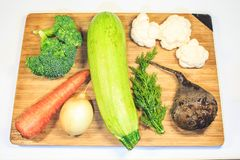 Fresh vegetables lie on a wooden board. Courgettes, carrots, beets, brocali, cauliflower, onions, parsley. stock photos