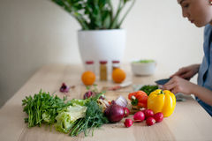 Fresh vegetables lying on the kitchen table. On the kitchen table lying the vegetables for salad, in the background woman cut vegetables for salad Stock Photo