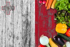 Fresh vegetables from Malta on table. Cooking concept on wooden flag background royalty free stock photos