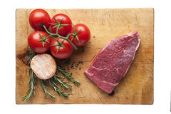 Fresh vegetables and meat on cutting board. Rosemary, tomatoes and old cheese Stock Photo