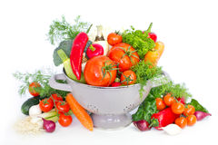 Fresh vegetables in metal colander. Over white Royalty Free Stock Photos