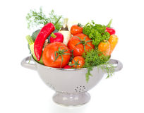 Fresh vegetables in metal colander. Over white Royalty Free Stock Image
