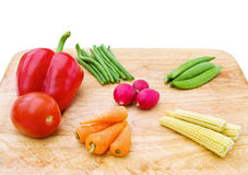 Fresh vegetables mix. Baby carrots, baby corn, sugarsnaps, beans, tomato and pepper on a wooden chopping board Royalty Free Stock Photos