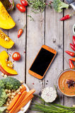 Fresh vegetables with mobile cell phone on a wooden background. Royalty Free Stock Images