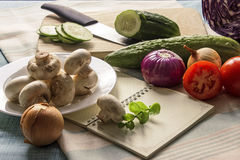 Fresh vegetables and mushrooms on the table with knife and notep. Fresh vegetables and mushrooms are on a kitchen table. Sliced cucumber on a cutting board with Royalty Free Stock Photography