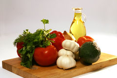 Fresh vegetables and olive oil on plate. Fresh raw vegetables and olive oil on wooden plate Stock Photography