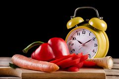 Fresh Vegetables On A Wooden Kitchen Board And Retro Clock On Wooden Board And Desk Royalty Free Stock Photos