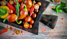 Fresh vegetables - organic pepper, paprika and cherry. On the chalkboard and an old wooden table royalty free stock images