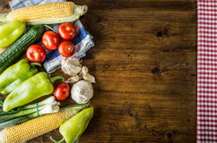 Fresh vegetables. Overhead view of a assortment of farm fresh vegetables, Green pepper, garlic, corn, onions, tomatoes, cucumbers.  Stock Photo
