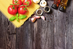 Fresh vegetables and pasta on dark wood Royalty Free Stock Photos