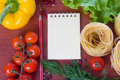 Fresh vegetables,pasta and a notebook Stock Images