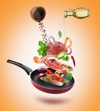 Fresh vegetables with pieces of beef meat, spices and oil flying. Into a pan stock illustration