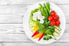 Fresh vegetables plate with feta cheese, cherry tomatoes, cucumber, celery, sweet pepper and basil in a plate on wooden background Stock Photo