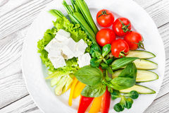 Fresh vegetables plate with feta cheese, cherry tomatoes, cucumber, celery, sweet pepper and basil in a plate on wooden background Stock Photos