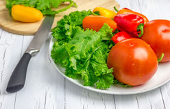 Fresh vegetables on the plate and a wooden board with vegetables on background. Fresh vegetables on the white plate and a wooden board with vegetables on Stock Photo