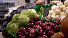 Fresh Vegetables with Price Tags on Supermarket Shelves. Cabbage, Onions, Potatoes, Pumpkin are Sold in Store.