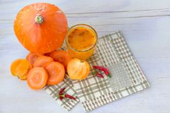 Fresh vegetables with pumpkin and a glass of sea buckthorn juice stock photo
