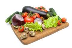 Fresh vegetables and quail eggs on a cutting board on a white ba Royalty Free Stock Images
