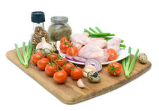 Fresh vegetables, quail eggs and raw chicken wings isolated on w. Fresh vegetables, spices, quail eggs and raw chicken wings on chopping board isolated on white Royalty Free Stock Image