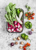 Fresh vegetables - radishes, cherry tomatoes, pepper, onion and garlic on a light background. Top view Stock Photo