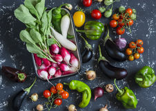 Fresh vegetables - radishes, tomatoes, peppers, onions, garlic, eggplant on a dark background, top view. Raw ingredients for cooking Stock Photography