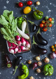 Fresh vegetables - radishes, tomatoes, peppers, onions, garlic, eggplant on a dark background, top view. Raw ingredients. For cooking Royalty Free Stock Photo