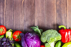 Fresh vegetables red cabbage and broccoli, cucumbers and peppers, tomatoes and basil. On dark wooden background. Farm organic products. Top view horizontal Stock Photography