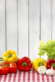 Fresh vegetables on red checkered table cloth. Wooden background. Copy space, selective focus Royalty Free Stock Photography