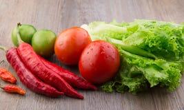 Fresh vegetables: red chilli, birds eye chilli, lettuce, red tomato and green tomato Stock Photos