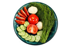Fresh vegetables on the round plate on a white background. Fresh tomatoes, cucumbers, dill and an onion on the round plate isolated on a white background Stock Image
