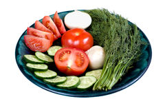 Fresh vegetables on the round plate on a white background. Fresh tomatoes, cucumbers, dill and an onion on the round plate isolated on a white background Stock Photo
