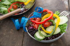 Fresh vegetables salad on  bowl with measuring tape over wooden Royalty Free Stock Images