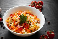 Vegetables salad with cabbage and carrot in bowl on a dark wooden background. Fresh vegetables salad with cabbage and carrot in bowl on a dark wooden background Royalty Free Stock Photo
