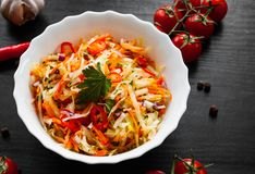 Vegetables salad with cabbage and carrot in bowl on a dark wooden background. Fresh vegetables salad with cabbage and carrot in bowl on a dark wooden background Royalty Free Stock Images
