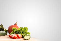 Fresh vegetables and salad ingredients. Standing ready for cooking on a wooden kitchen table in the bottom left corner of the frame with large copyspace on a Stock Images