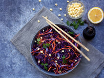 Fresh vegetables salad with purple cabbage, carrot, sprouted mung, parsley on grey clay plate on dark background. Cole Slaw Salad Stock Photo