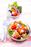 Fresh vegetables in salade. Greek salad in a transparent bowl and ingredients. vertical format Royalty Free Stock Photos