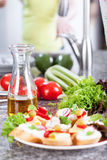 Fresh vegetables and sandwiches on granite worktop Royalty Free Stock Photo