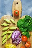 Fresh vegetables are sliced on a cutting board, cherry tomatoes, spinach, cabbage, celery. Vegetarian dinner. Top view. Fresh vegetables are sliced on a cutting Royalty Free Stock Photos