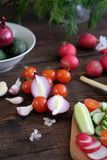 Fresh vegetables sliced for a salad on a cutting board. On an old wooden table Royalty Free Stock Photos