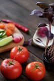 Fresh vegetables sliced for a salad on a cutting board. On an old wooden table Royalty Free Stock Images