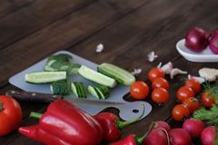 Fresh vegetables sliced for a salad on a cutting board. On an old wooden table Stock Image